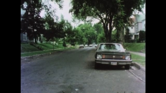 UNITED STATES 1970s: Car parked on side street. Car drive on road. Car drives behing green station wagon. Car merges to left lane to pass green station wagon.