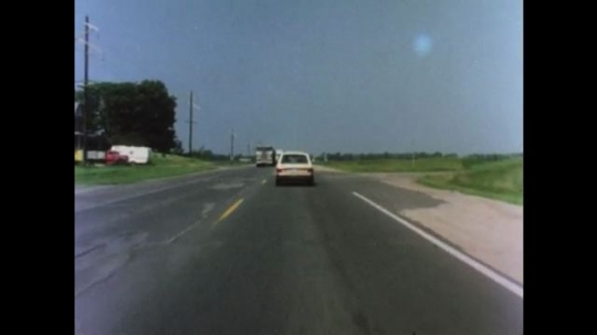 UNITED STATES 1970s: Car drives on road swerves in lane as cars pass in other lane. Car swerves in lane. Car swerves to the right as truck passes on left.