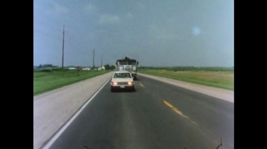 UNITED STATES 1970s: Car moves to the right as truck and car passes on left.