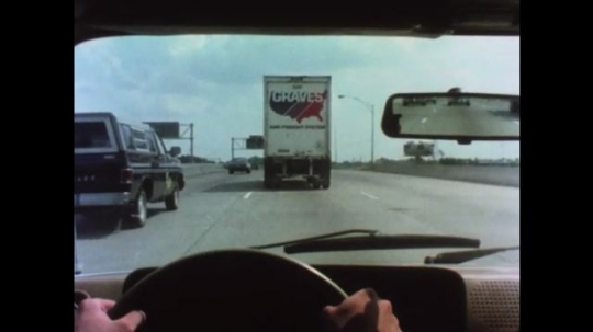 UNITED STATES 1970s: Hands on steering wheel drives behind truck. Truck turns on left directional signal. Truck merges into left lane. Car merges into left lane. Cars pass car in left hand lane.