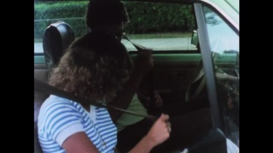 UNITED STATES 1970s: Man and woman put on seatbelts. Car drives on road. Stop at yellow light. Car drives bext to truck. Van drives on road. Car moves to right as truck and car pass in the left lane.