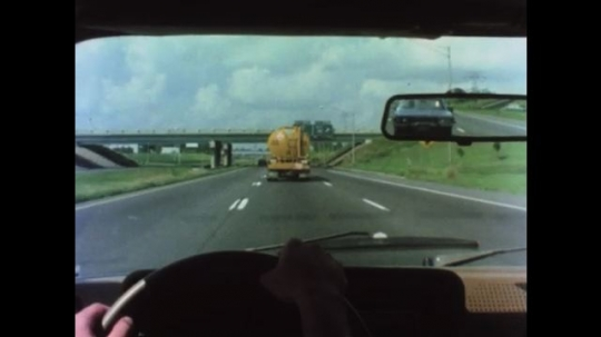 UNITED STATES 1970s: Hands on steering wheel drives. Hands on steering wheel and shifter passes car. Car merges onto highway as truck merges. Car flashes headlights. Car drives on road.