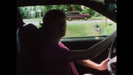 UNITED STATES 1970s: Woman drives car. Woman looks to left. Woman makes U-turn. Car drives on road.