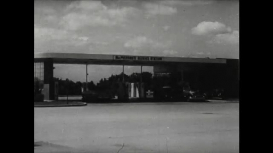 UNITED STATES 1950s: car pulls out of gas station. Car arrives at gas station pump. Sign for MacPherson