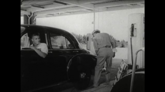 UNITED STATES 1950s: Service station man opens petrol cap on car. Man takes petrol pump hose. Driver opens car door. Young man talks to attendant filling car.