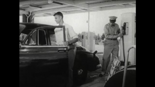 UNITED STATES 1950s: Boy gets into car. Gas station attendant replaces fuel cap. Attendant polishes side of car with cloth. Driver moves car from pump to road side. Driver gets out of car.