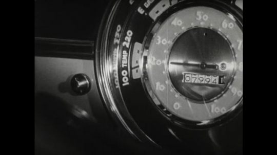 UNITED STATES 1950s: close up of speedometer in car. Car drives up steep hill. Driver changes gear on car. View through windscreen as car approaches brow of hill.