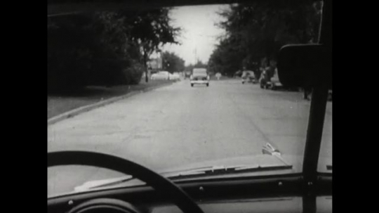 UNITED STATES 1950s: view of road and cars through windscreen of vehicle. Side view of car at junction. Man looks left and right at junction. Close up of pedal.