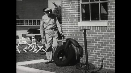 UNITED STATES 1950s: man and boy walk around side of building. Man picks up tire. Man puts foot in tire. Man talks to boy.