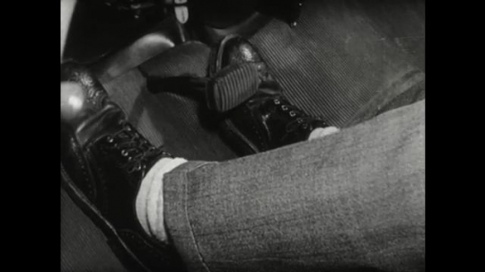 UNITED STATES 1950s: close up of foot on car pedal. Man fills bottle with fluid at car door. Rear view of parked car.