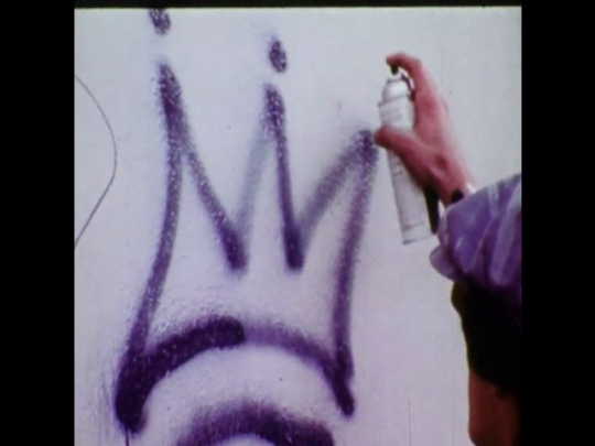 "UNITED STATES 1970s: Young man graffitis a wall then runs away. Title of film shows, ""Graffiti - Fun or Dumb?"". Shot of skyscraper."