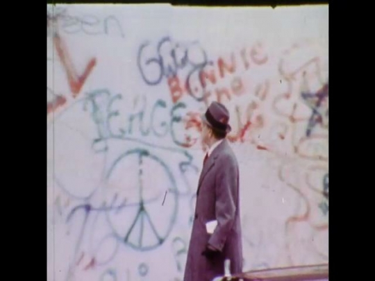UNITED STATES 1970s: Businessman walks in front of graffitied wall. Young man spray paints graffiti onto wall. Graffitied subway travels along tracks towards camera.