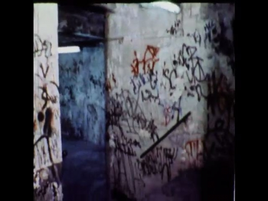 UNITED STATES 1970s: Graffiti covered walls of metro station, subway traveling down tracks, man walking down stairway covered in graffiti.