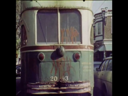 UNITED STATES 1970s: Graffitied trolley drives away, a worker paints over wall graffiti.