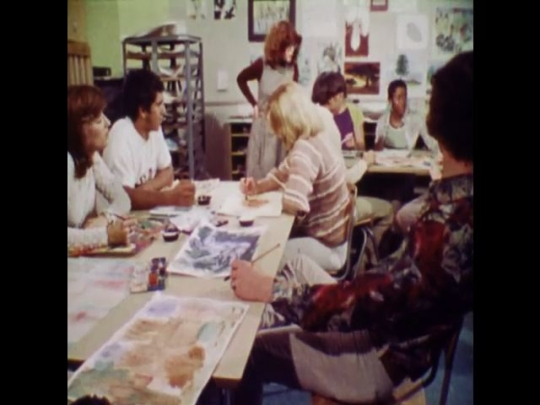 UNITED STATES 1970s: A diverse group of students paint on canvases at desks and talk with the instructor and each other, young man scrubs at camera.