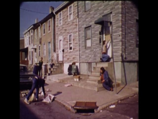 UNITED STATES 1970s: A group of people clean up outside of an apartment, older woman talks to camera, young man paints a picture on a canvas.