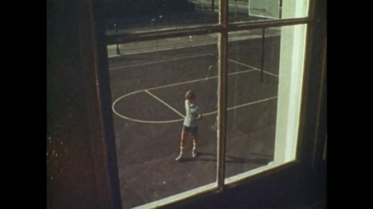 UNITED STATES 1970s: Window view of boy on basketball court. Boy walks in slow motion. Different views of boy throwing rock. Boy throws rock. Window glass breaks.