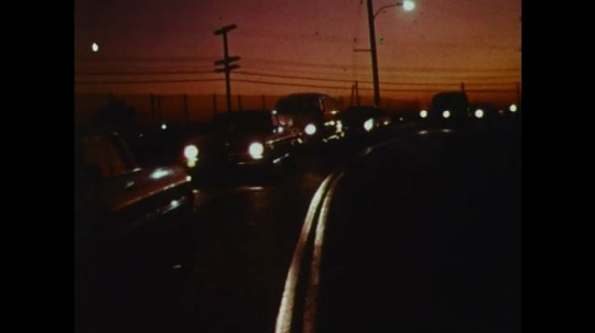 UNITED STATES: 1970s: cars drive on road at night. Men clock into work. Workers at car factory. Man tests car design.