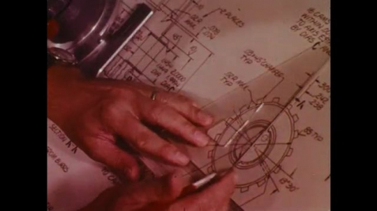 UNITED STATES: 1970s: engineers draw designs on paper. Workers in lab. Part testing for cars.