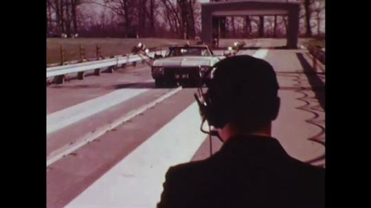 UNITED STATES: 1970s: engineers collect data on cars at proving ground site. Cars damaged in test drive.