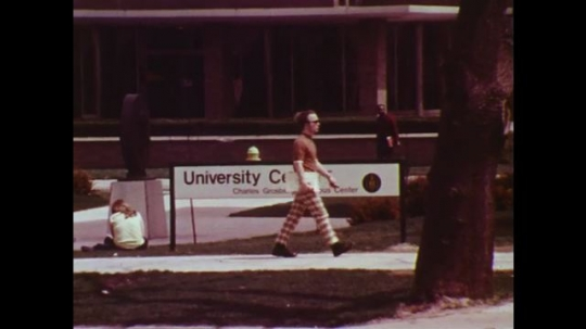 UNITED STATES: 1970s: highway research at university. Students outside university. Cars drive past building.