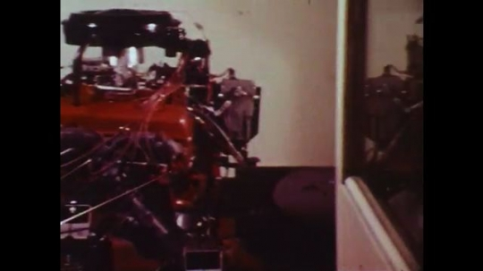 UNITED STATES: 1970s: man measures pollution from car in lab. Engine modification.