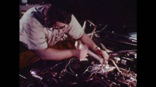 UNITED STATES: 1970s: worker adjusts car engine with spanner. Engine of car. Vehicle Emission Laboratory sign