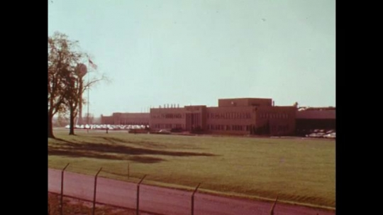 UNITED STATES: 1970s: view across car manufacture plant. Man tests substances in lab. Pollution monitoring.