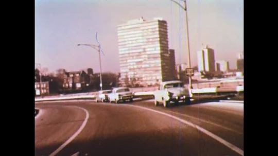 UNITED STATES: 1950s: Cars drive along road. Houses in suburb. Shopping mall.