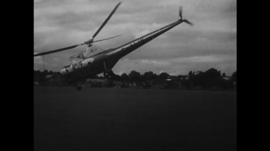 UNITED STATES: 1950s: helicopter blades in slow motion. Helicopter takes off in slow motion