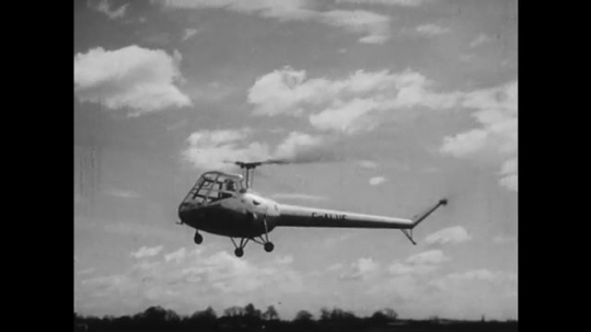 UNITED STATES: 1950s: Skeeter helicopter. Railway lines. Fast helicopter