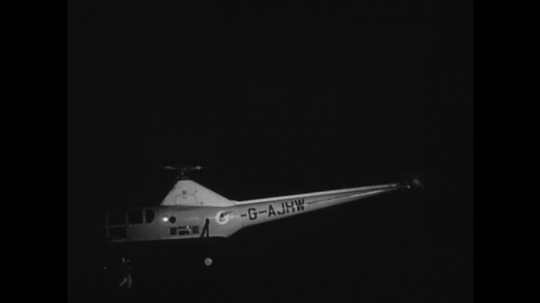 UNITED STATES: 1950s: Sikorsky helicopter at night. Sikorsky helicopter transports mail. Men load mail onto helicopter