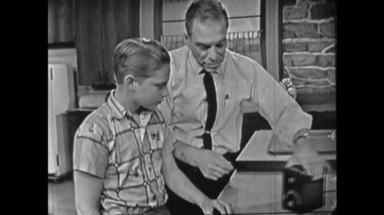 United States 1960s: man does capillary refill test on boy's thumb. Man pinches boy's thumb. Boys thumb becomes white. Boys thumb turns pink.