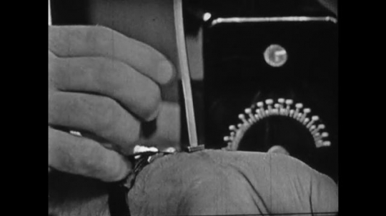 United States 1960s: boy feels for pulse in wrist. Boy holds machine, Close up of metre on machine. Man explains concept to boy.