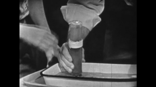 United States 1960s: hand squeezes tube. Hand covers hole in tube. Man points to take around tube.