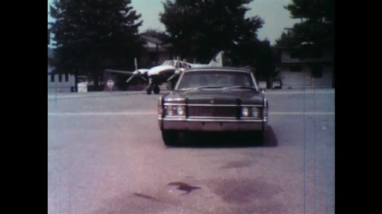 United States: 1950s: car pulls up next to plane. Men get out of car. Men walk to helicopter.