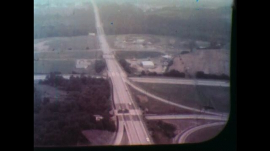 United States: 1950s: view of road from helicopter. Helicopter flies over road. Cars on road. Man looks out of helicopter window.