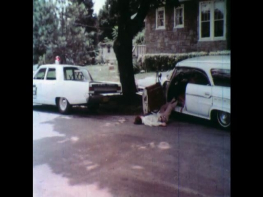 United States: 1950s: Body next to car after crash. Police vehicle next to car crash. Glass fragments on seat of car after crash. Hand polishes car.