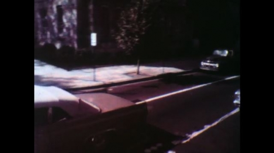 United States: 1950s: vehicles on road seen from above. Lady and trolley on ground. Body on floor. Food on floor after pedestrian run over.