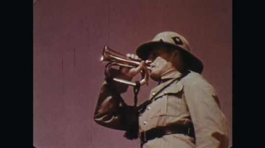 INDIA: 1960s: man in uniform blows bugle. Soldiers march in town square.