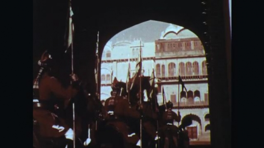 INDIA: 1960s: Men on horse back ride under arch. Street filled with people and elephants parading.