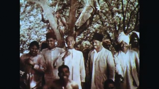 INDIA: 1960s: men stand under tree and wave at camera. Boys play together. Guns fire. Soldiers on parade with rifles.