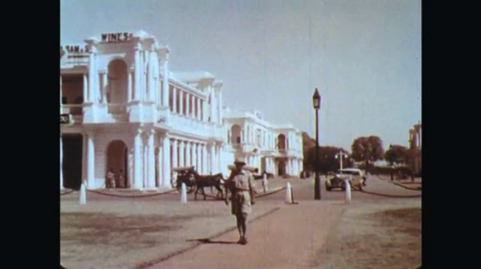 INDIA: 1960s: man in uniform with shorts walks along road. Car drives along street. People walk in park.