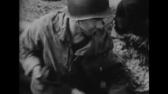 EUROPE: 1940s: soldier digs trench in sand. Soldiers rest on beach. Injured man on stretcher. Men cross land during battle.