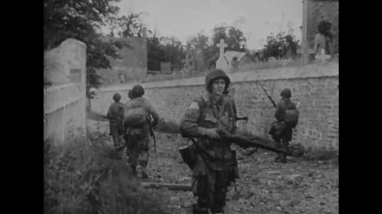 EUROPE: 1940s: soldiers walk by church. Soldiers talk to civilians. Men dress wounds. Supplies on ground.