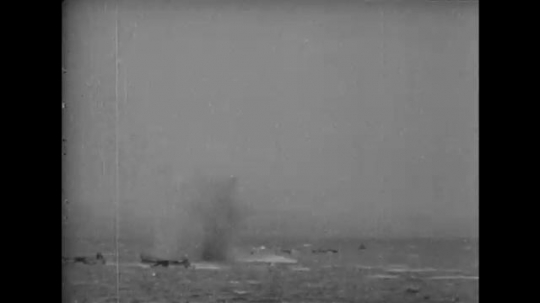 EUROPE: 1940s: ships hit by bombs. Planes fly above ships. Soldiers climb down ropes. Guns fire missiles.