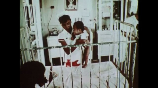 UNITED STATES 1970s: Nurse caring for crying baby / Woman giving a shot to a baby / Ship with red cross sailing / Nurse caring for patient / Teacher uses chalkboard / Man sat at desk drawing