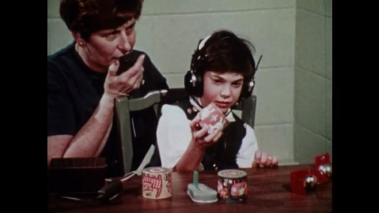 UNITED STATES 1970s: Child with headphones manipulating objects whilst woman speaks into a microphone / Man plugging wire into a machine and inspecting results on screen