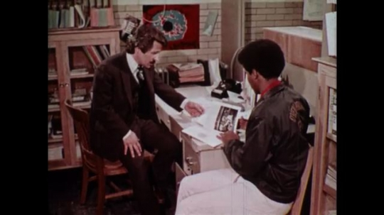 UNITED STATES 1970s: Man reads a book and discusses it with another man at a desk in an office / Man enters the Pennsylvania State Employment Service building / Man has discussion with his family