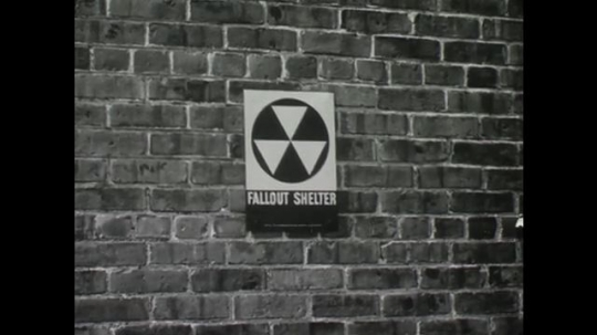 UNITED STATES: 1950s: Fallout shelter symbol on wall of building. People walk past building